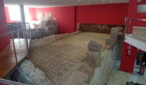 Junto al portal de un edificio moderno y elevado, se accede a los bajos de éste: una casa romana